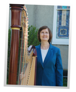 Elaine Bryant of Harp Shadows standing with her harp